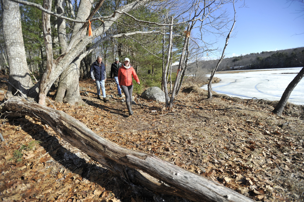 From left: Archie Bonyun, Dennis Dunbar and Anna Christie-Carnicella of the Kennebec Estuary Land Trust walk through Squam Creek Preserve on Westport Island Thursday (Staff photo by Shawn Patrick Ouellette)