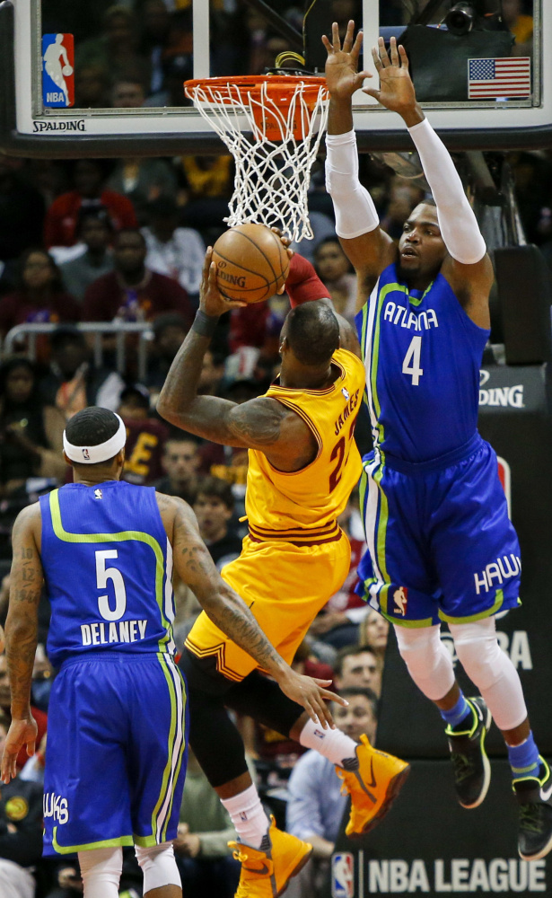 Atlanta forward Paul Millsap, right, leaps to defend against Cleveland's LeBron James during the Cavaliers' 135-130 win on Friday in Atlanta.