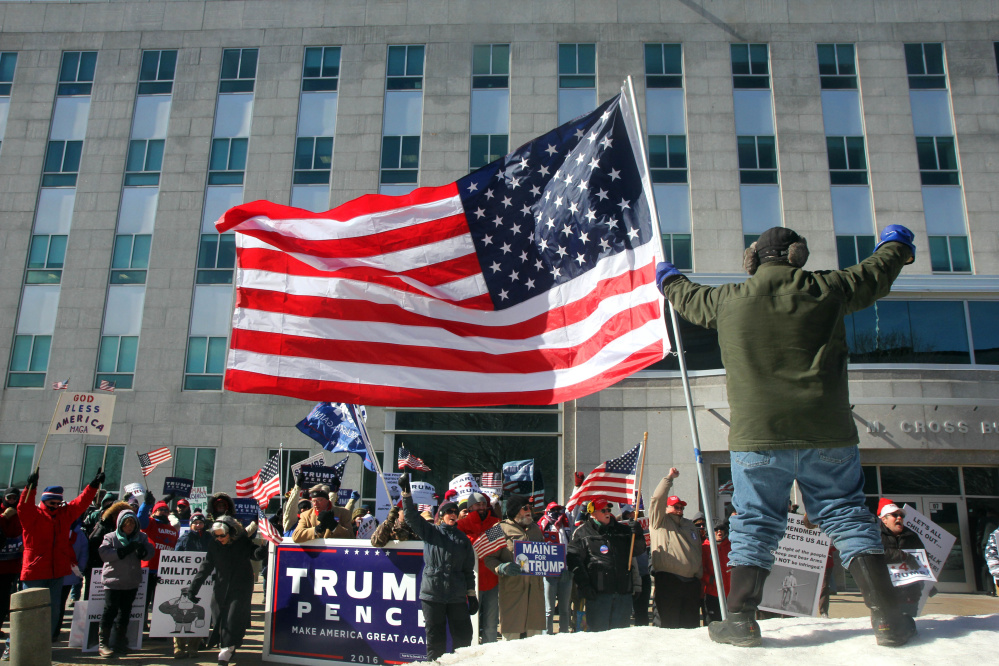 Donnie Heald, of Lincolnville, holds a large American flag Saturday in front of the Burton M. Cross State Office Building as Trump supporters brave below-zero wind chill at a March 4 Trump rally in Augusta. The event was part of a nationwide show of support for President Donald Trump.