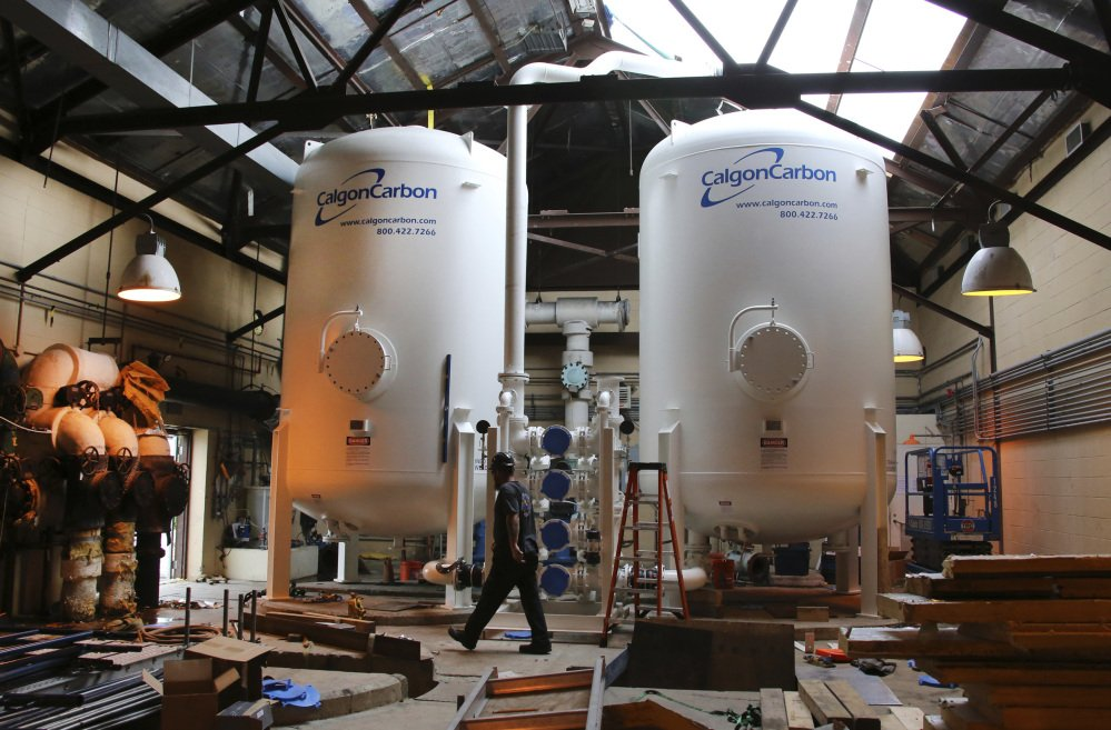 A worker walks by two large carbon filtration tanks at the Pease International Tradeport water treatment facility in Portsmouth, N.H. More than 1,500 people have learned their blood contains elevated levels of a chemical that has been linked to health problems.