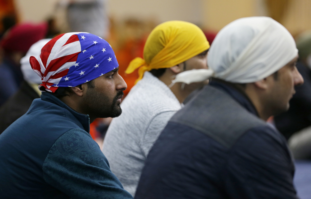 A man wears a head covering with the stars and stripes of a U.S. flag as he attends Sunday services at the Gurudwara Singh Sabha of Washington, a Sikh temple in Renton, Wash.