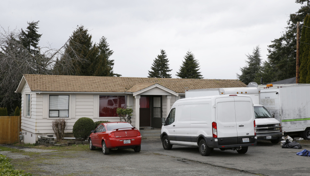 Vehicles sit parked Sunday at the home and driveway where a Sikh man was shot in the arm Friday in Kent, Wash. Authorities say a Sikh man said a gunman shot him as he worked on his car and told him