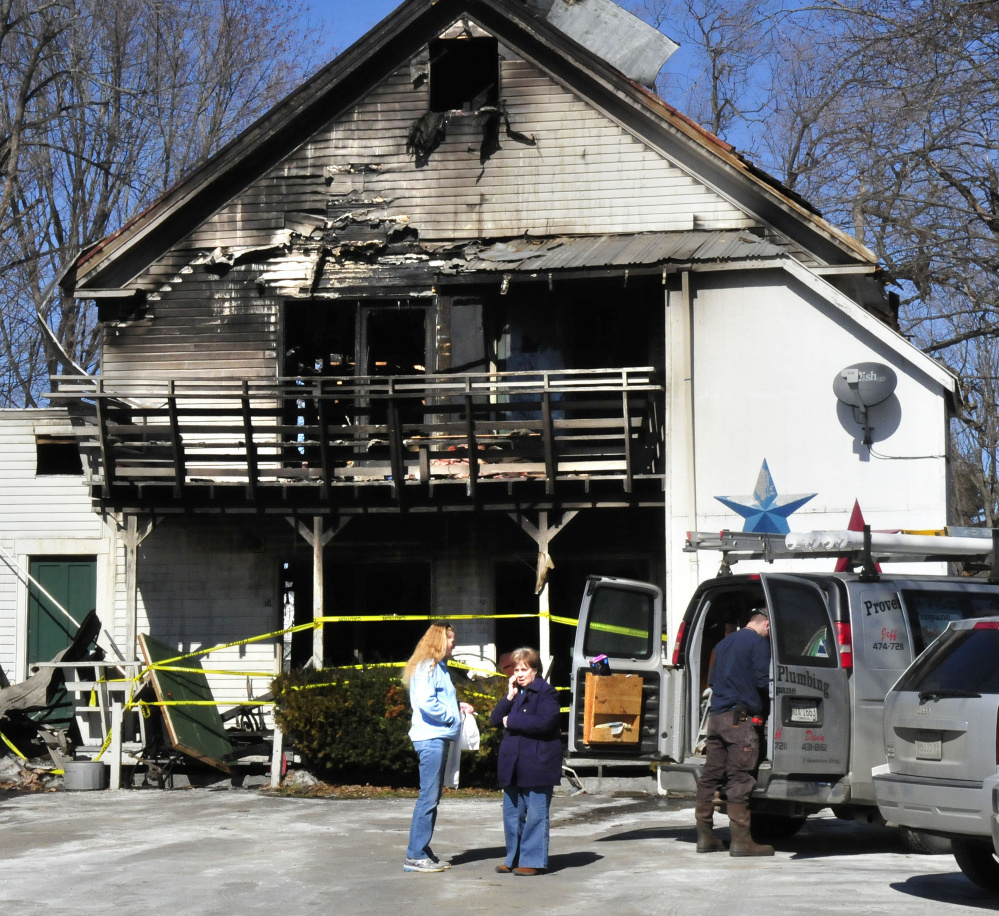 Virginia Weems, right, who owns the apartment complex at 152 Main St. in Madison that was heavily damaged in a blaze, stands beside tenant Barbara Turner on Monday. Four apartments were gutted, while Turner's unit sustained smoke damage.