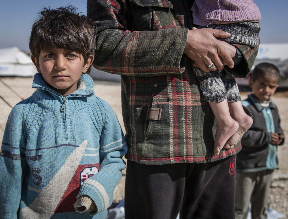 A Syrian school teacher stands with his son and daughter in a camp. A new report by Save the Children says Syrian children are showing symptoms of