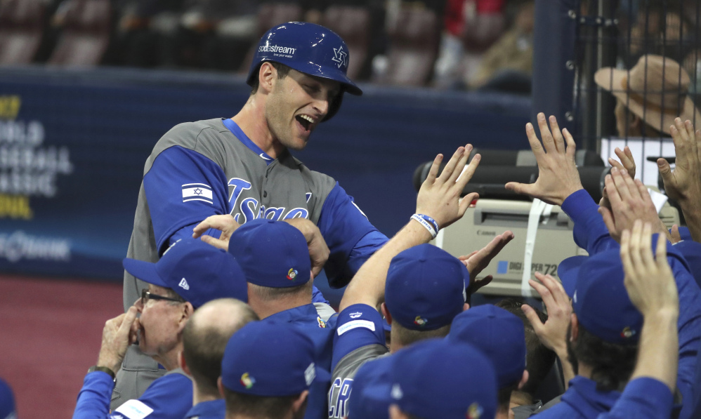 Israel's Nate Freiman celebrates with teammates after scoring on a bases-loaded walk in the second inning of a 2-1 first-round win over South Korea in the World Baseball Classic on Monday at Gocheok Sky Dome in Seoul, South Korea.
