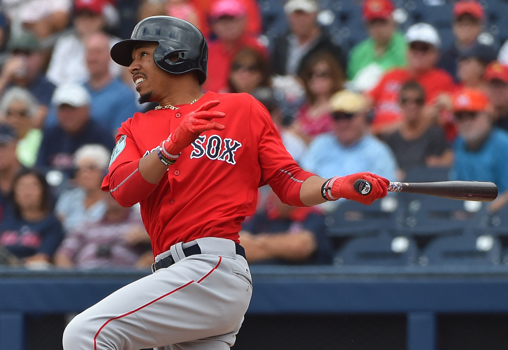 Mookie Betts of the Red Sox hits a first-inning home run Tuesday against the Nationals at The Ballpark of the Palm Beaches in West Palm Beach, Fla. The Red Sox won, 5-3.