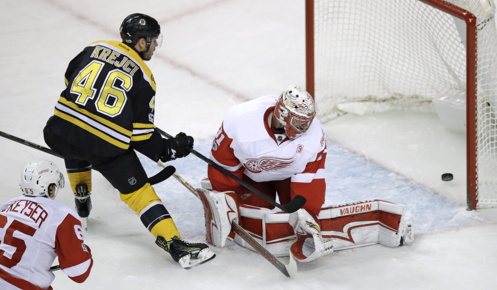Bruins center David Krejci pokes the puck past Red Wings goalie Jared Coreau for a goal during the first period.