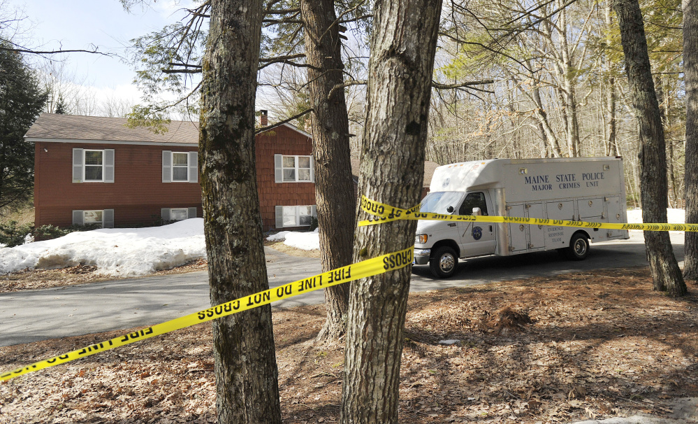 A Maine State Police van is parked Thursday outside the home of Matthew and Sue Kim Coito on Campground Road in Arundel. His body was found Wednesday in the kitchen. Hers was found Friday about 375 yards into the woods near the home.