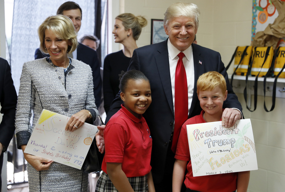 Associated Press/Alex Brandon President Trump and Education Secretary Betsy DeVos pose with fourth graders Janayah Chatelier, 10, left, Landon Fritz, 10, after they received cards from the children, during a tour of Saint Andrew Catholic School last Friday.