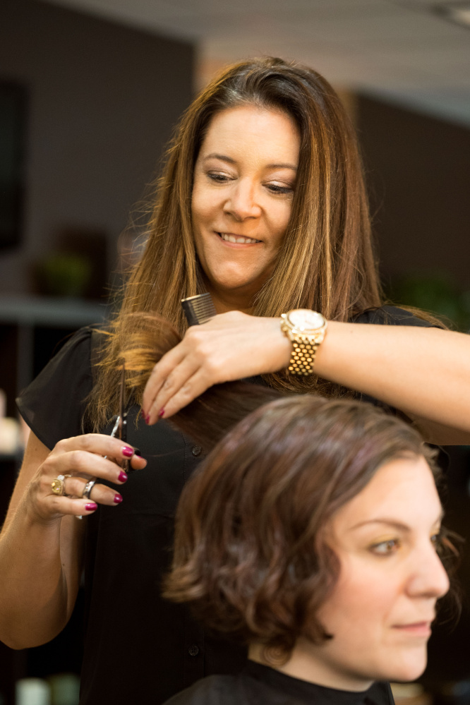 Christy Legere cuts a client's hair at Magnolia's Salon in Sanford, which she owns with her sister, Kelly Clark. In the Skinny on Skin program, they were trained to spot early signs of skin cancer in their clients.