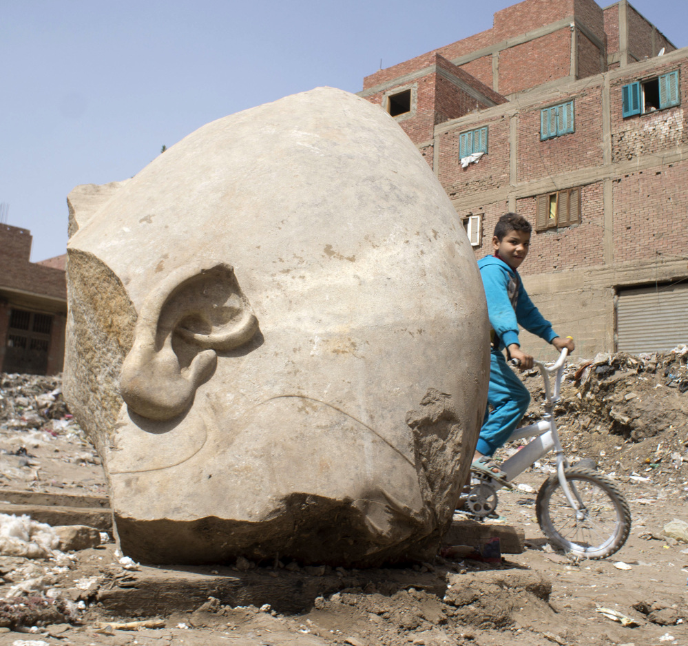 A boy rides his bicycle past a recently discovered statue in a Cairo slum that may be of pharaoh Ramses II, in Cairo, Egypt, on Friday.