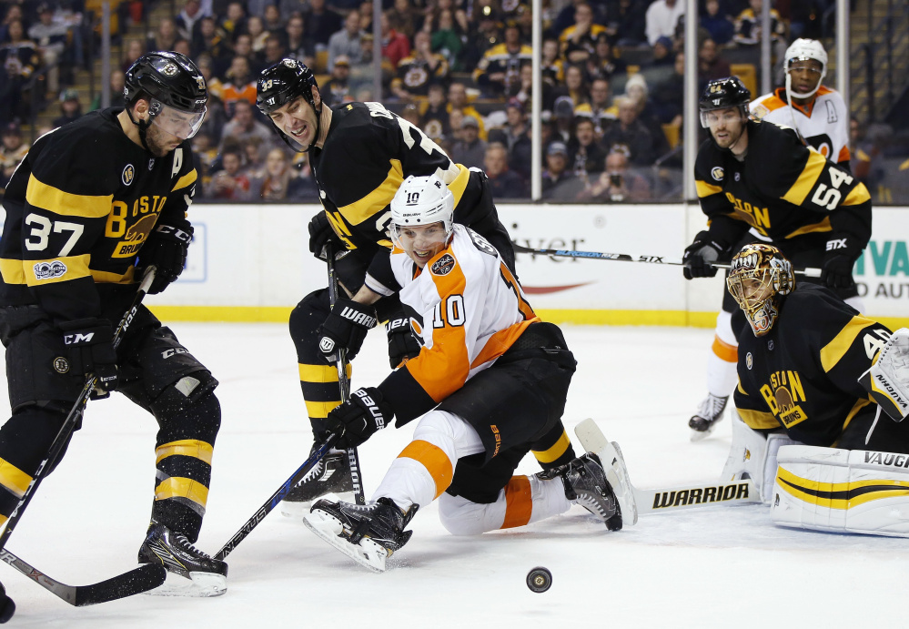 Philadelphia's Brayden Schenn, center front, battles Boston's Patrice Bergeron, left, and Zdeno Chara, center back, for a rebound during the first period of the Bruins' 2-1 win Saturday in Boston.