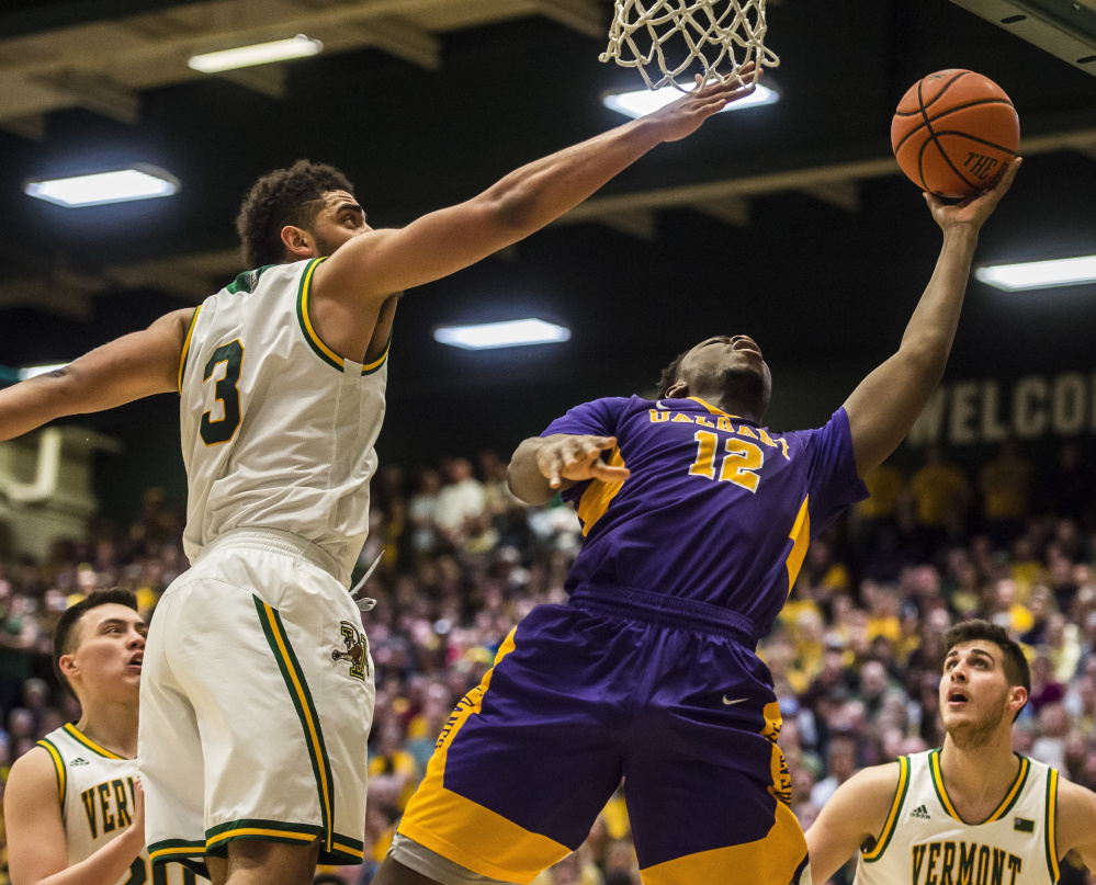 Devonte Campbell of Albany slips past Anthony Lamb of Vermont for a layup Saturday. Vermont won the America East championship and an NCAA tournament berth with a 56-53 victory at home.