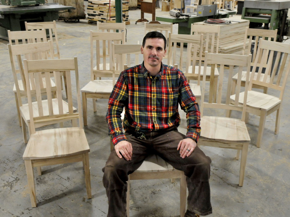 Maine Made Furniture owner Tim Lovett sits in a chair built for Sunday River ski resort at his furniture shop. Lovett closed on the company last fall and opened a location in Wilton. He hopes to do his hiring locally.