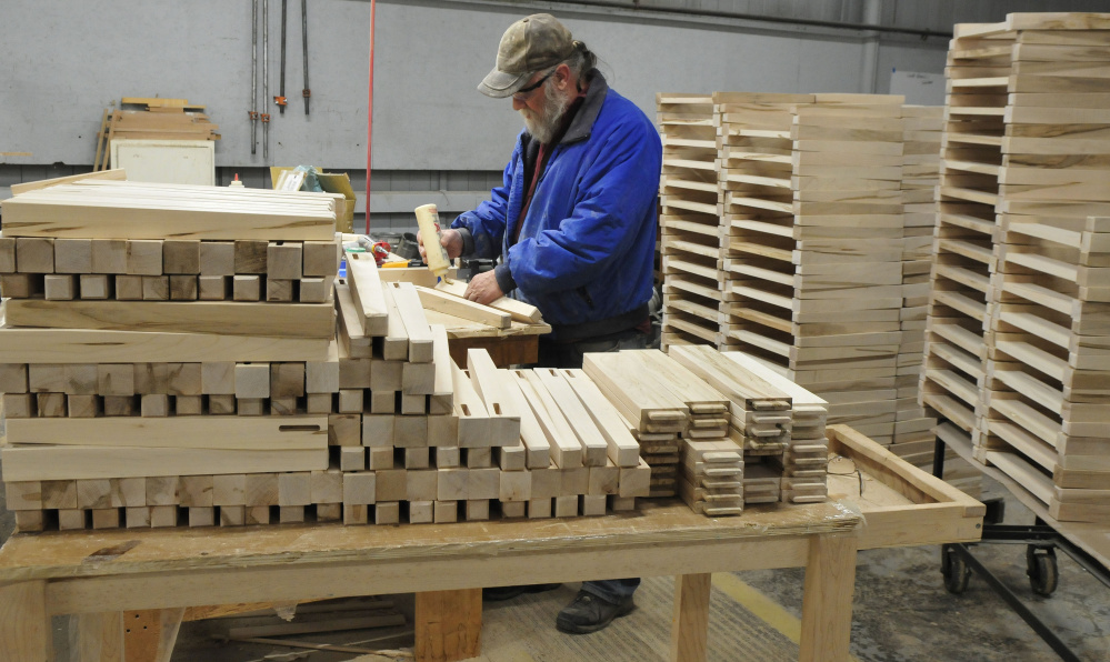 Ernest Edmunds glues chair legs at Maine Made Furniture in Wilton. Among the furniture-maker's new contracts is a 1,000-piece furniture deal with Sunday River.