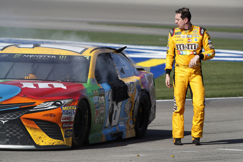 Kyle Busch looks at his smoking car at the end of the NASCAR race Sunday at Las Vegas Motor Speedway. One NASCAR official said Busch and Joey Logano likely won't face harsh penalties after a fight on pit road.