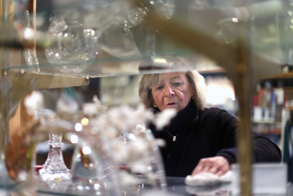 Mary Ellen Pallozzi, owner of Ireland's Crystal & Crafts, dusts off her crystal selections. Photos by Ben McCanna/Staff Photographer
