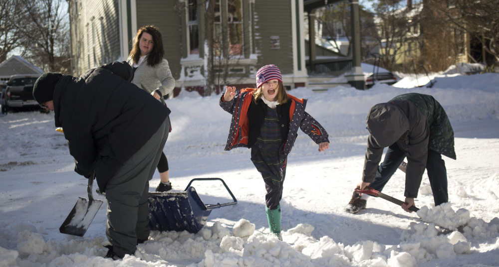 Lola Fitzgerald, 5, jumps over a pile of snow as her family shovels a driveway in Portland's West End on Wednesday. The storm contributed to one of the city's snowiest seasons in recent years.