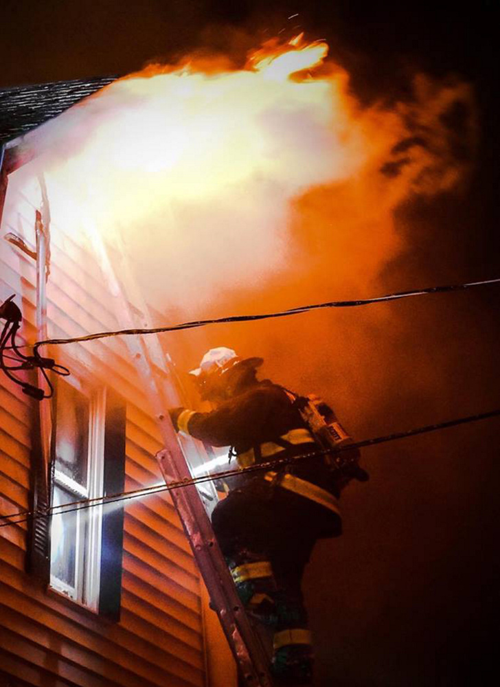 Monmouth firefighter Josh Reny uses a ground ladder to fight a fire that burned a single-family Tuesday night in home in Monmouth.