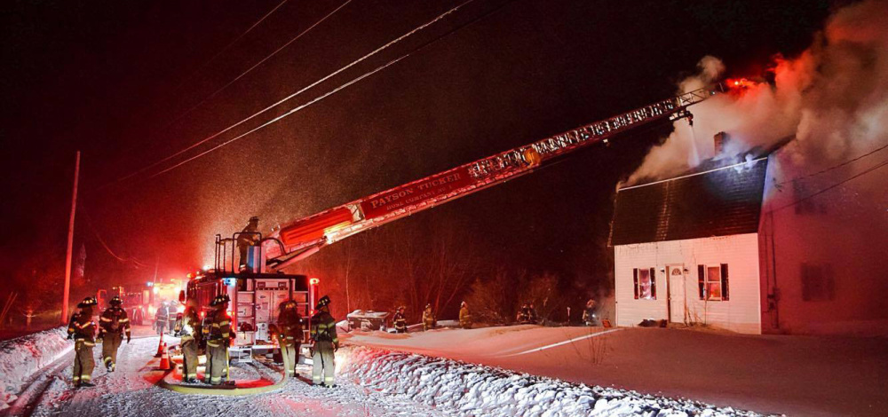 Firefighters from Winthrop use a ladder truck late Tuesday to spray a stream of water through an opening in the roof of a home at 554 Route 135 in Monmouth.