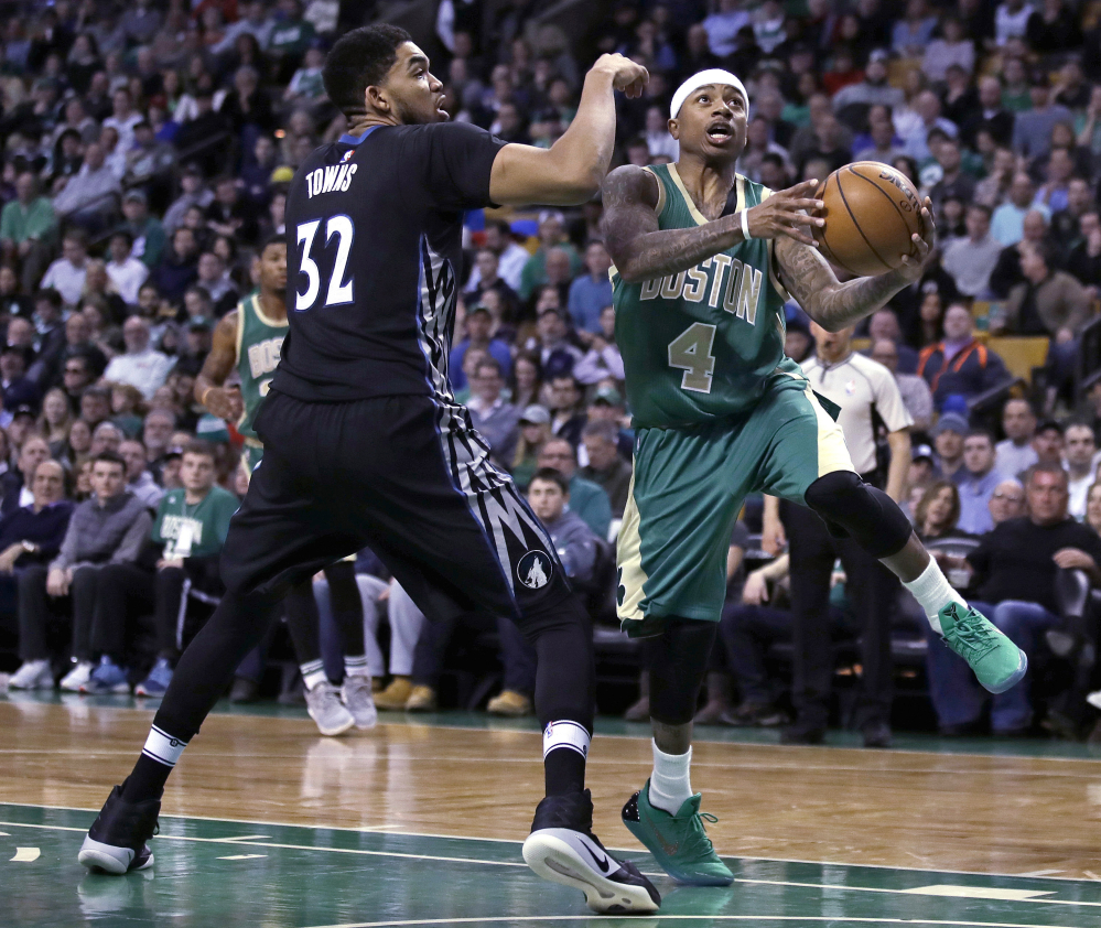 Boston Celtics guard Isaiah Thomas drives to the basket against Minnesota center Karl-Anthony Towns during Wednesday's game in Boston. Thomas will miss the next two games for Boston with a bone bruise to his right knee. (Associated Press/Charles Krupa)