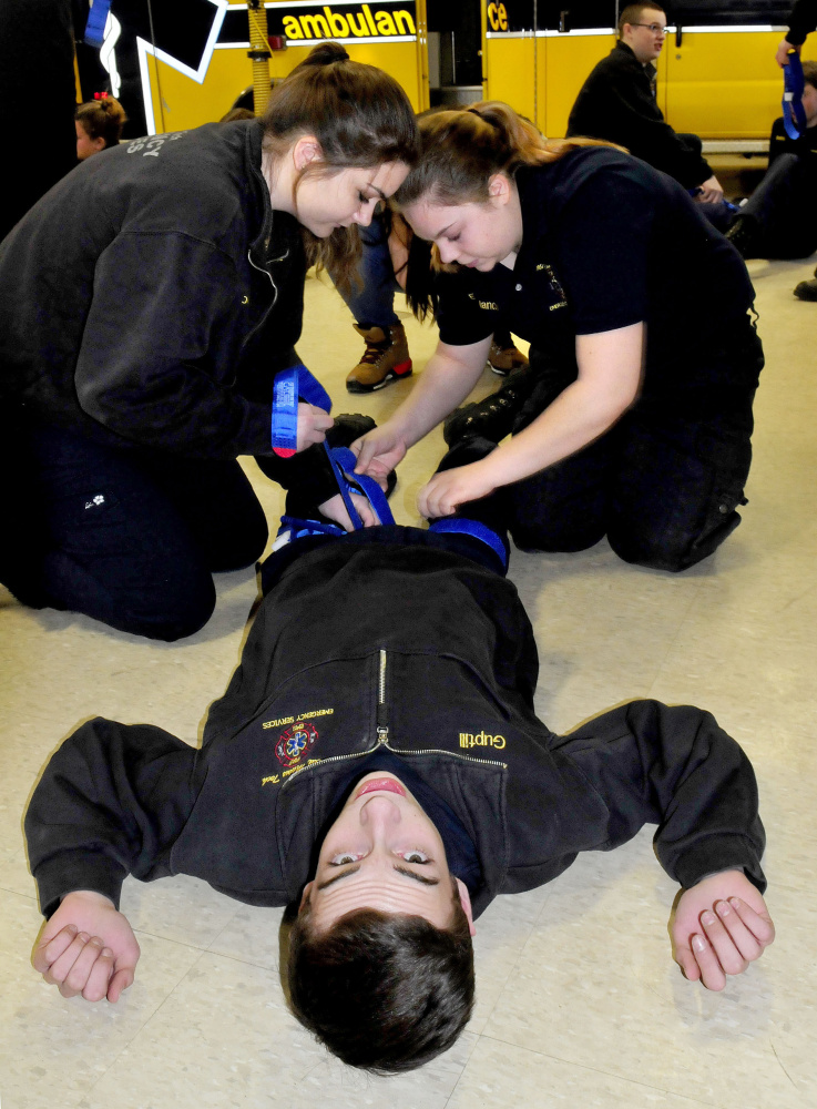 Mid-Maine Technical Center students Ashley Leighton, left, and Emily Melancon apply tourniquets to Hunter Guptill on Thursday during training on stopping bleeding.