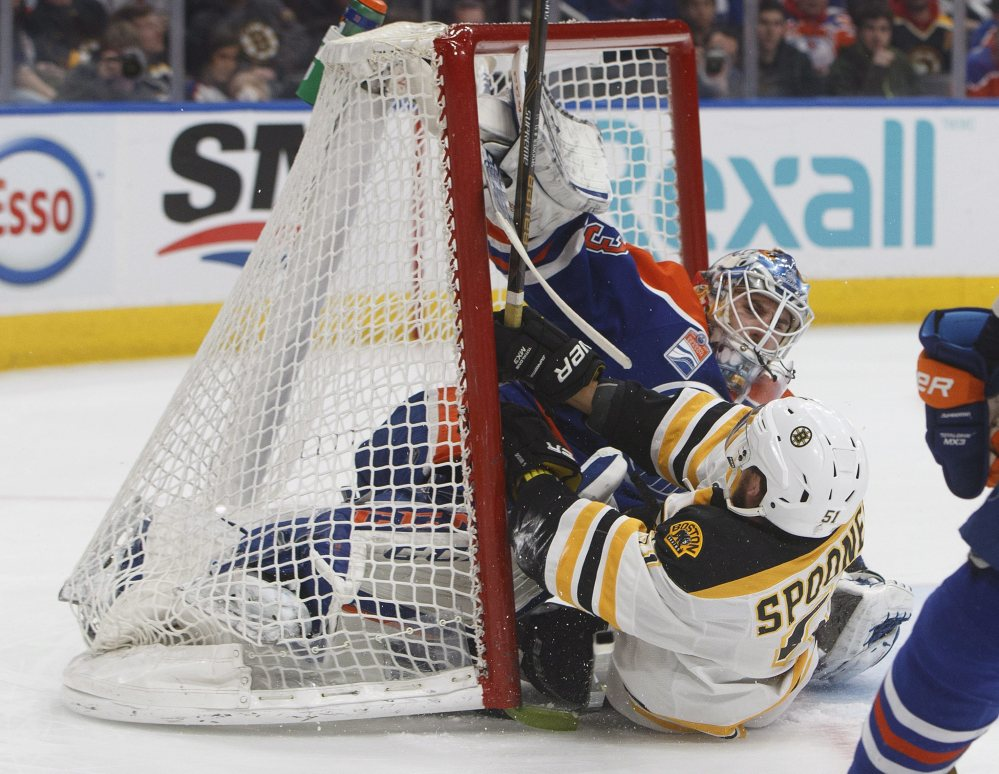 Boston's Ryan Spooner crashes into Oilers goalie Cam Talbot in the first period Thursday night in Edmonton, Alberta.