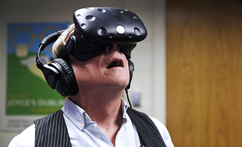 Joseph Nugent, a Boston College English professor, wears virtual reality goggles at the school's virtual reality lab in Boston. College students in Boston are developing a virtual reality game based on James Joyce's ponderous tome