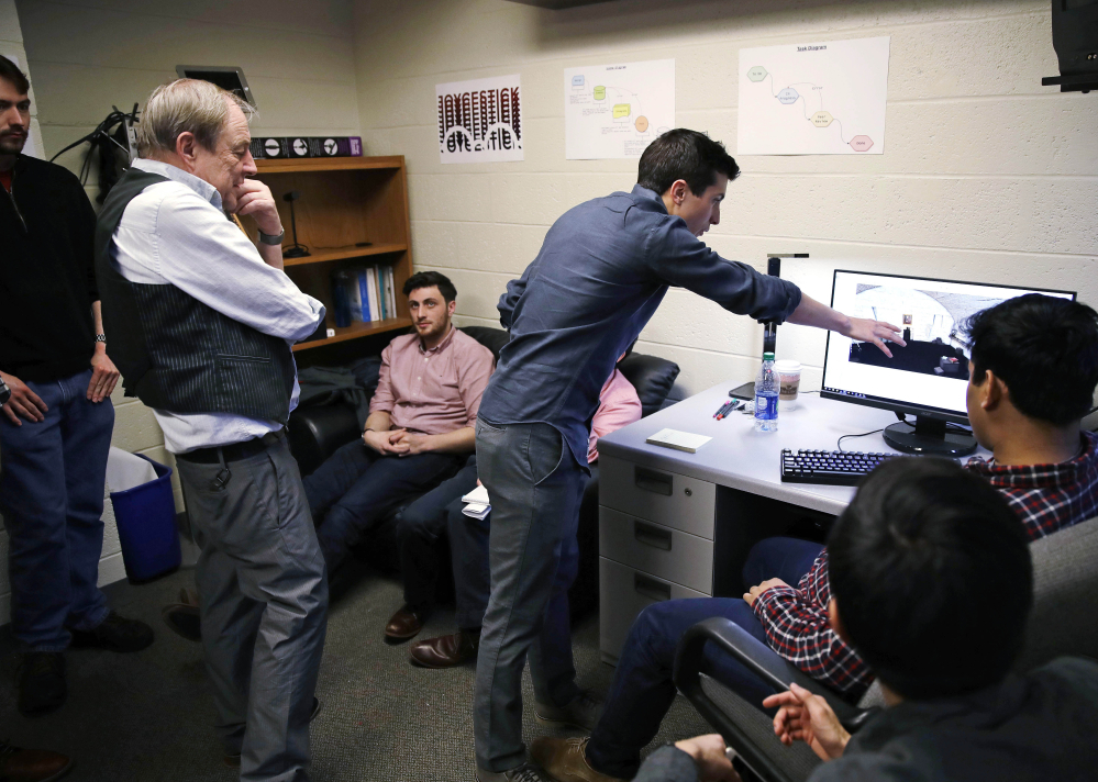 Joseph Nugent, an English professor at Boston College, left, watches as student Evan Otero points out a graphic on a work station at the school's virtual reality lab. Students are developing a virtual reality game based on James Joyce's