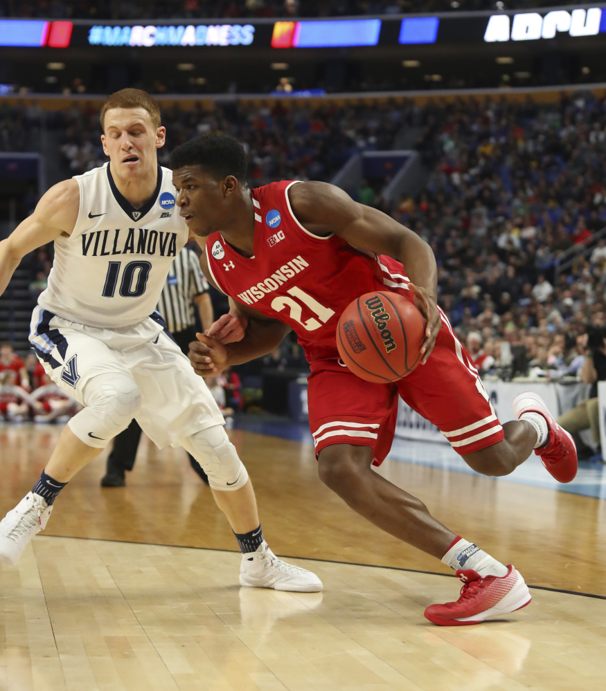 Wisconsin guard Khalil Iverson, right, drives to the basket against Villanova guard Donte DiVincenzo during the first half of a second-round men's college basketball game in the NCAA Tournament on Saturday in Buffalo, N.Y. Wisconsin knocked off the defending national champion, 65-62. (Associated Press/Bill Wippert)