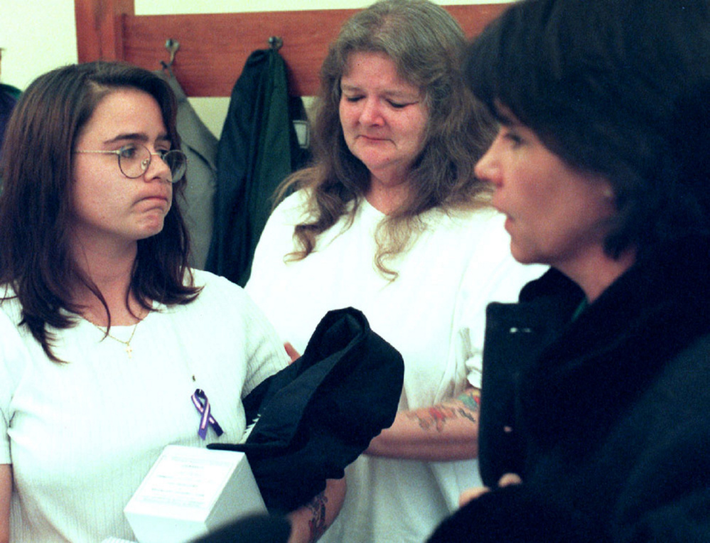 Christy Baker, left, listens to then-Rep. Julie Ann O'Brien, R-Augusta, right, who publicly apologized on behalf of the state for the death of Baker's daughter in 2001. Baker, now named Christy Darling, holds the ashes of Logan Marr. Baker's mother, Katlynn Badger, is in the background.