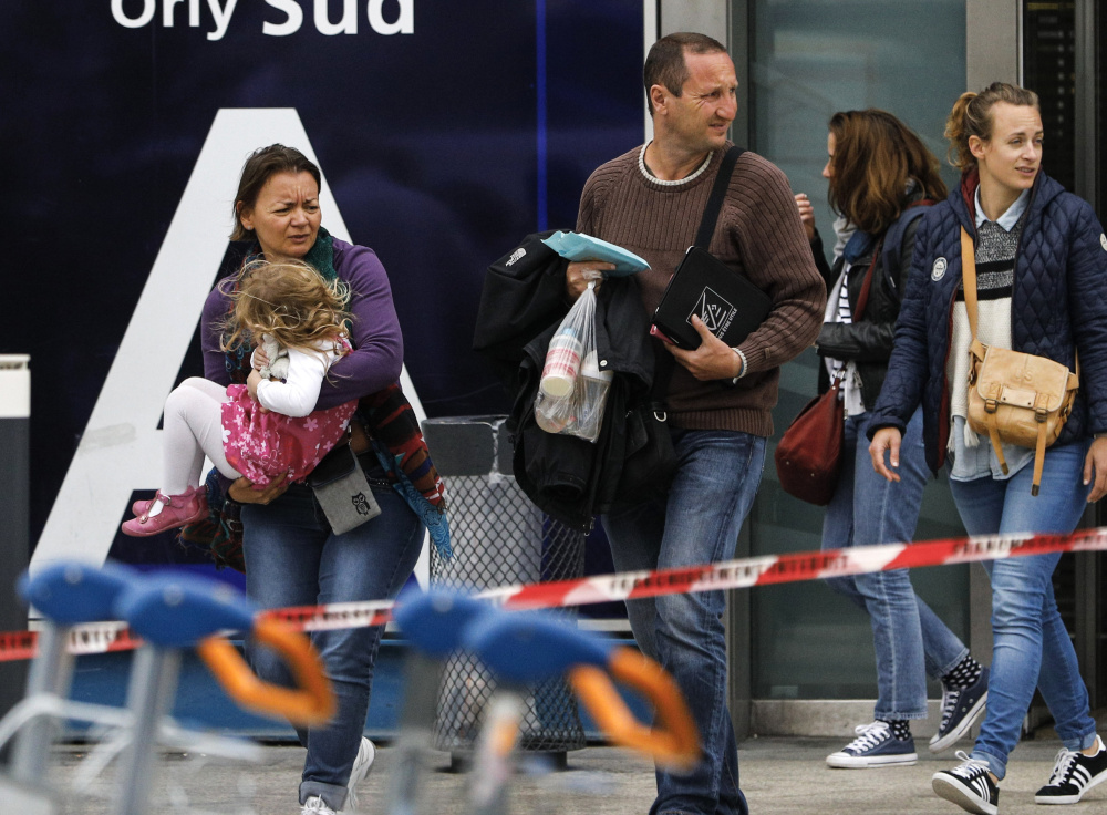 Travelers evacuate Paris' busy Orly Aiport, where French soldiers shot and killed a man who attacked one of their colleagues and tried to steal her rifle Saturday.