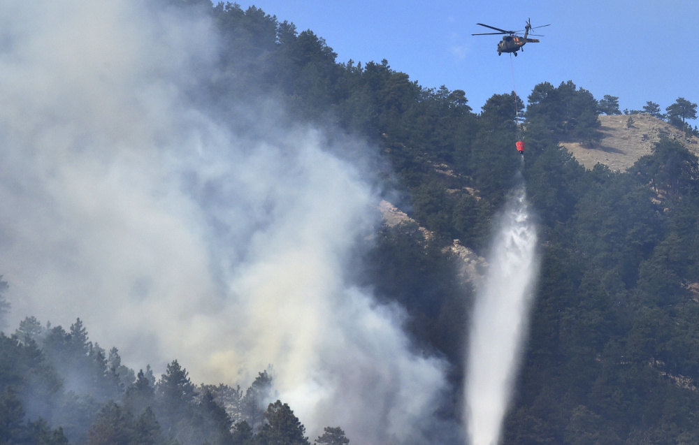 A helicopter drops water on the fire burning west of Boulder, Colo., on Sunday. The fire forced people from hundreds of homes early Sunday, authorities and residents said.