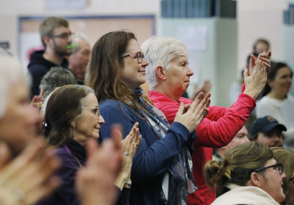 Audience members applaud the arrival of Rep. Chellie Pingree, D-Maine, at a health care town hall Sunday at King Middle School in Portland.