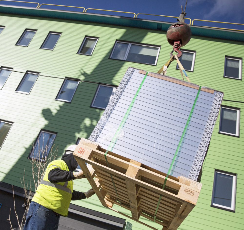 Dave Cleveland, of Keeley Crane Service, guides a pallet of solar panels as they are lifted to the roof in Portland.