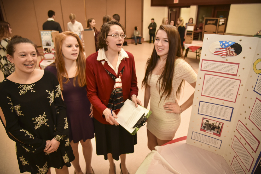 Monmouth Academy sophomores, left to right, Elizabeth Mason, Valerie Fullerton, social studies teacher Jocelyn Gray and student Mckenzie Stevens discuss the team's choice of interviewing Cold War-era veteran Richard Howard. The team created a poster including the history of the Cold War and interview details on what it was like to serve during this period in American history after World War II.
