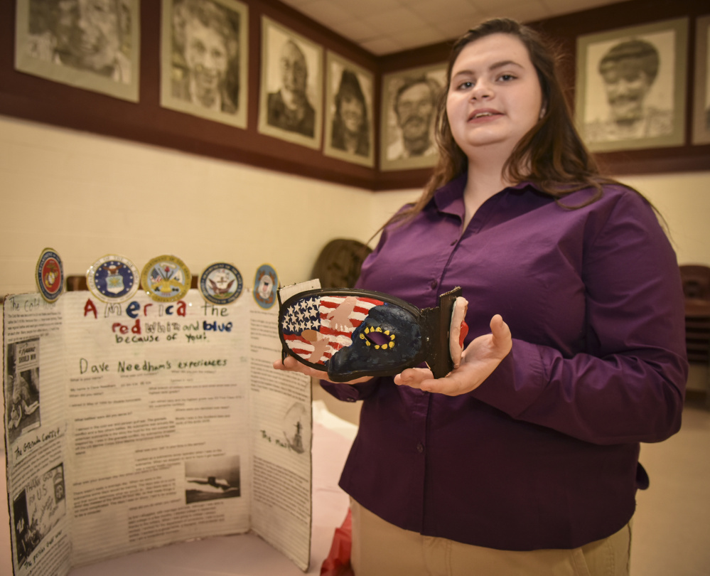 Monmouth Academy sophomore Jessica Withee shows off a mask she made in honor of veteran Dave Needham, a Navy sonar technician, the focus of her social studies project.
