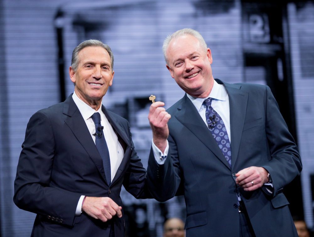 Howard Schultz, Starbucks chairman, left, gives incoming CEO Kevin Johnson the key to the original Pike Place Market store Wednesday during the shareholders meeting in Seattle.