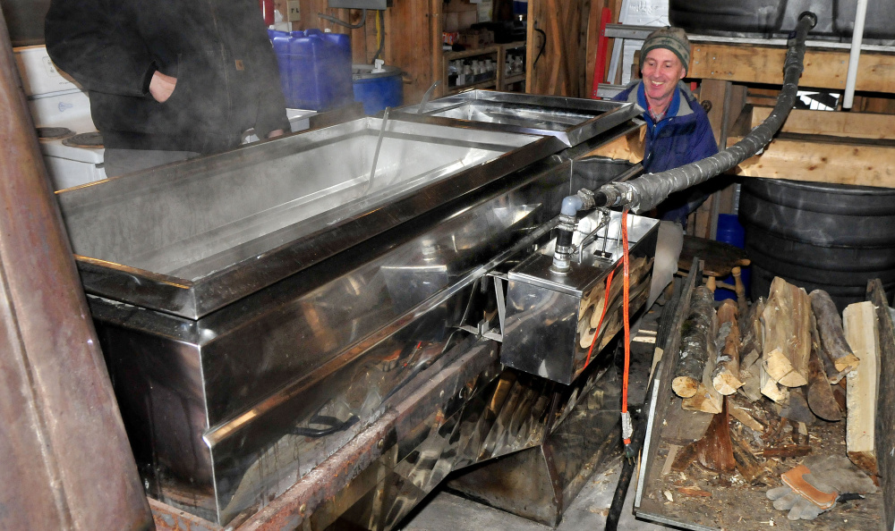 As steam rises from a wood-fired evaporator, John Ackley loads more wood while boiling maple syrup Monday at the Chez Lonndorf sap house on Burrill Hill Road in Skowhegan in preparation for the Maine Maple Sunday event this weekend.