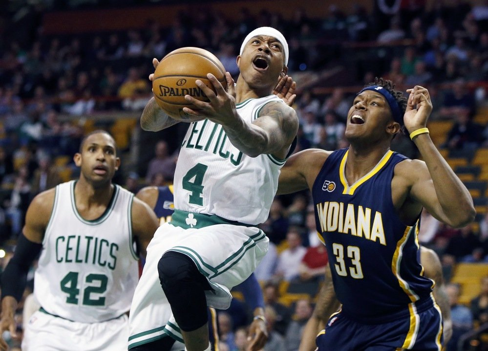 Isaiah Thomas of the Boston Celtics, center, goes up to shoot against Indiana's Myles Turner (33) during the first quarter of Wednesday's game in Boston. (Associated Press/Michael Dwyer)