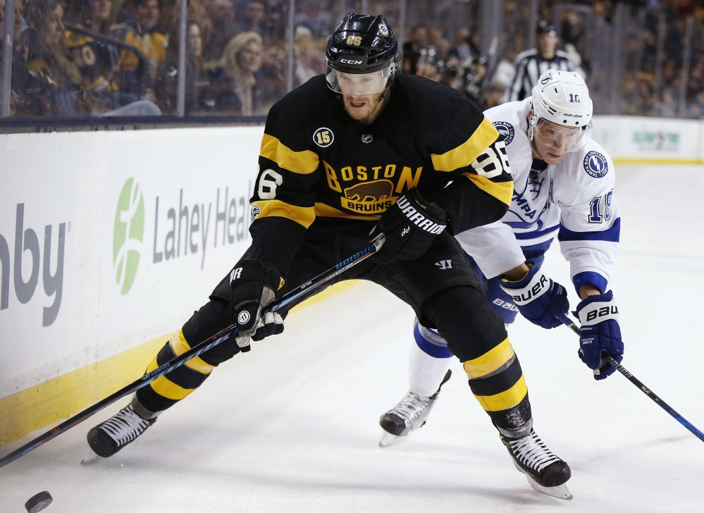 Bruins defenseman Kevan Miller looks to protect the puck from Ondrej Palat of the Tampa Bay Lightning during their game Thursday night in Boston. The Bruins lost their fourth straight, 6-3.