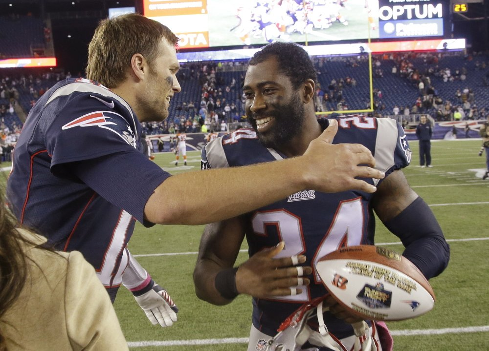 Darrelle Revis, right, hugs quarterback Tom Brady after a game against the Cincinnati Bengals on Oct. 5, 2014. According to numerous reports, the free agent cornerback Revis could soon return to New England.
