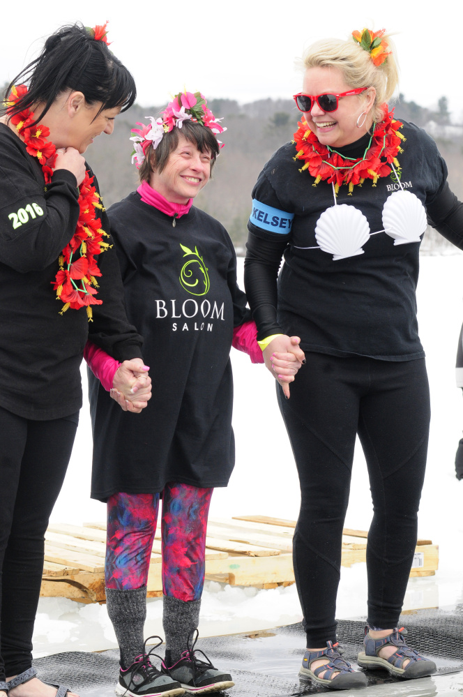 From left, Tricia Lynn Trial, Laura Lucas and Kimberly Stoneton get psyched up to jump into Maranacook Lake on Saturday during the Maine Law Enforcement Torch Run Ice Out Plunge on at Winthrop's town beach.