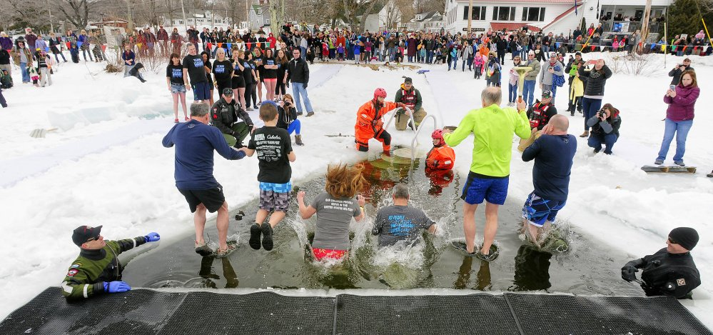 Jumpers leap into Maranacook Lake during the Maine Law Enforcement Torch Run Ice Out Plunge on Saturday at Winthrop's town beach.