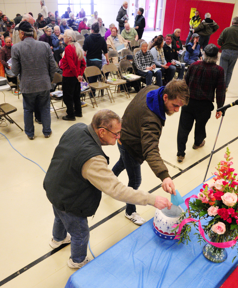 Residents put paper ballots into a container to vote Saturday during the China Town Meeting in the China Middle School gymnasium.