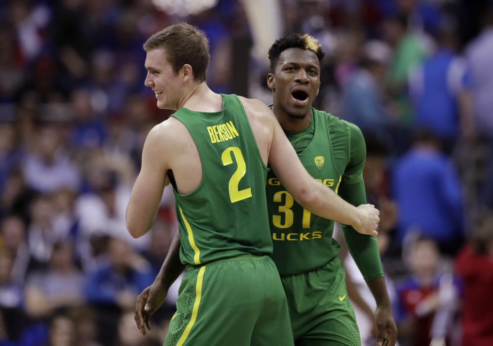 Casey Benson, left, celebrates with teammate Dylan Ennis during Oregon's 74-60 win over Kansas in the Midwest Region final Saturday night in Kansas City, Mo.