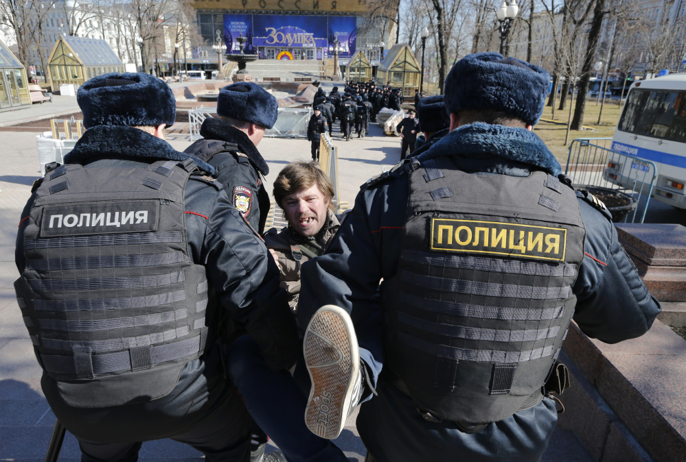 Police detain a protester in downtown Moscow on Sunday. Russia's leading opposition figure, Alexei Navalny, and his supporters held anti-corruption demonstrations throughout the country.