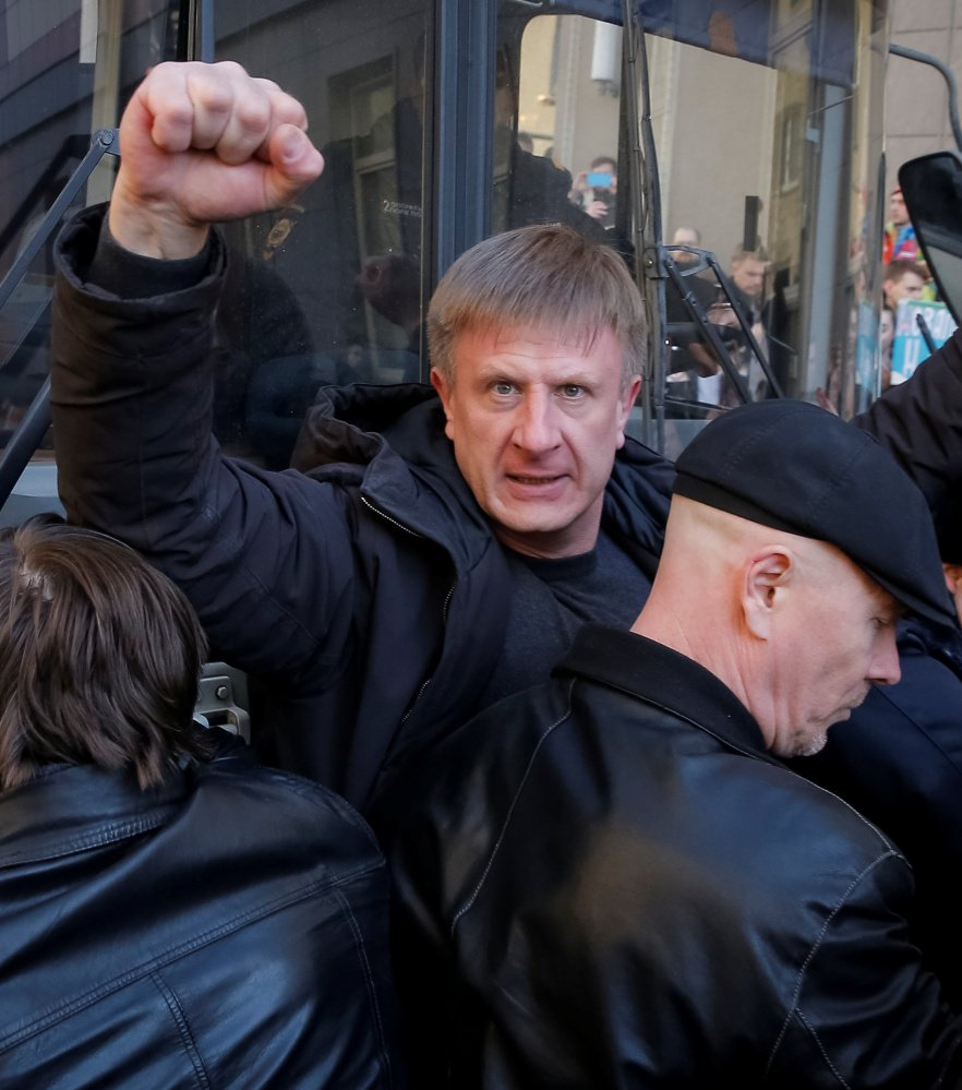 An opposition supporter gestures with a clenched fist as he blocks a police van transporting Alexei Navalny during the rally in Moscow.