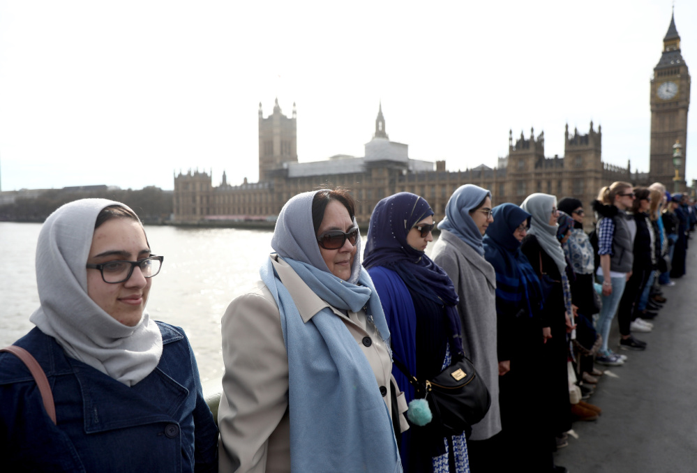 Participants in the Women's March gather on the Westminster Bridge to hold hands in silence Sunday to remember victims of the attack in London last week.