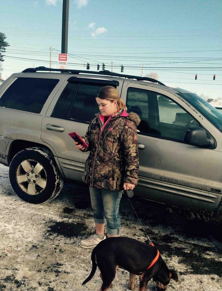 Nicole Bizier, 32, stands by her silver Jeep in the Pizza Hut parking lot with the dog she allegedly tried to sell to state animal welfare agents and Skowhegan police on Feb. 2.